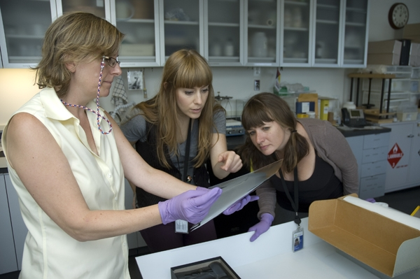 Sarah Stauderman, Susannah Wells, and Marguerite Roby examine and triage acetate and nitrate films f