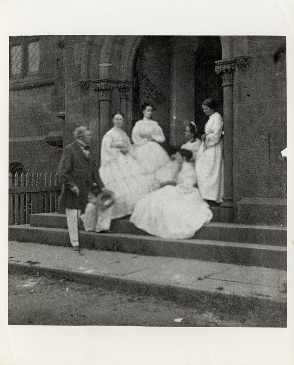 Secretary Joseph Henry with his wife, Harriet, and daughters standing at the east door to the Smiths