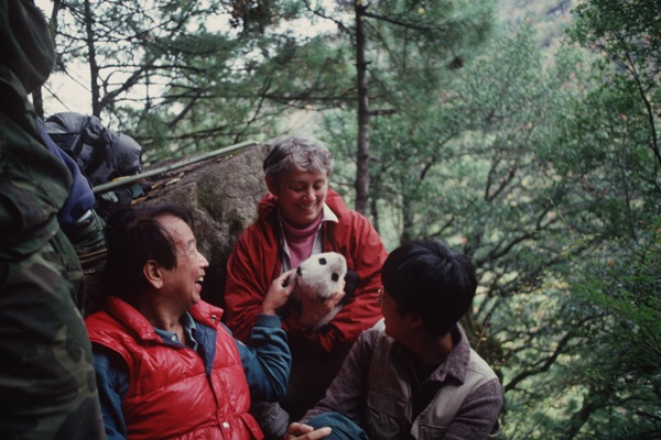 woman holding panda cub in forest with two people surrounding her, one petting the cub